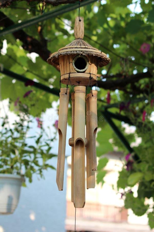 Carrilhões de vento de madeira da decoração do jardim com o aviário pequeno na parte superior cercada com flores e outras plantas foto de stock