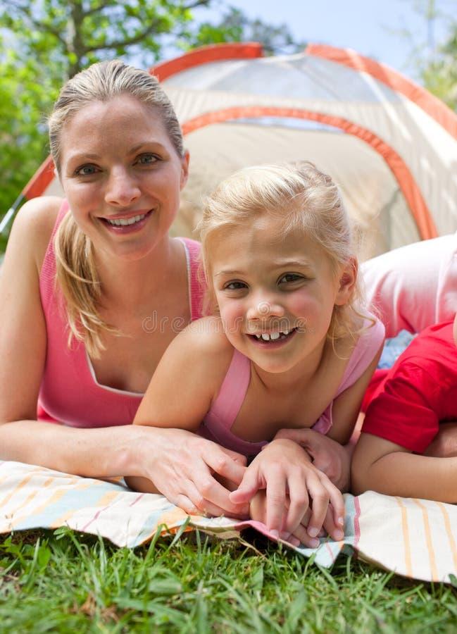 Carring Mutter und ihr Mädchen, die auf dem Gras liegen lizenzfreies stockfoto