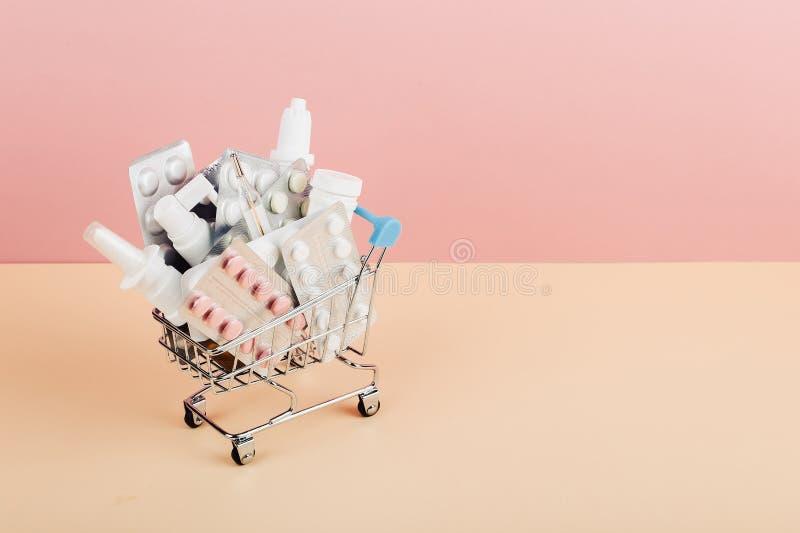 Carrinho de compras carregado com os comprimidos em um fundo amarelo cor-de-rosa O conceito da medicina e a venda das drogas Copi fotografia de stock royalty free