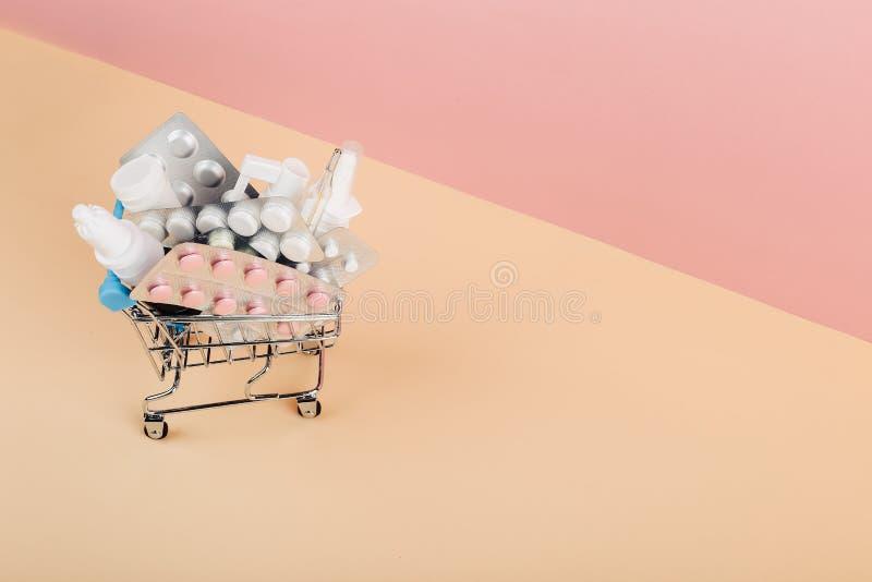 Carrinho de compras carregado com os comprimidos em um fundo amarelo cor-de-rosa O conceito da medicina e a venda das drogas Copi foto de stock royalty free