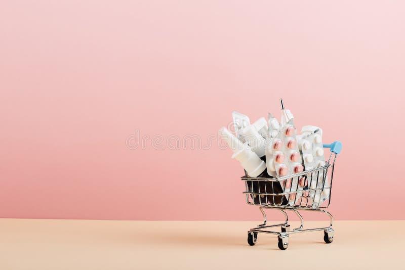 Carrinho de compras carregado com os comprimidos em um fundo amarelo cor-de-rosa O conceito da medicina e a venda das drogas Copi imagens de stock royalty free