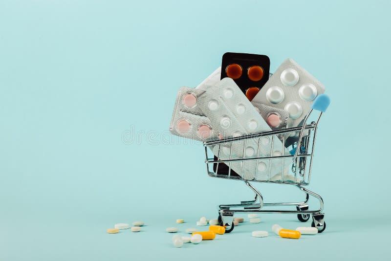 Carrinho de compras carregado com os comprimidos em um fundo azul O conceito da medicina e a venda das drogas Copie o espa?o imagens de stock