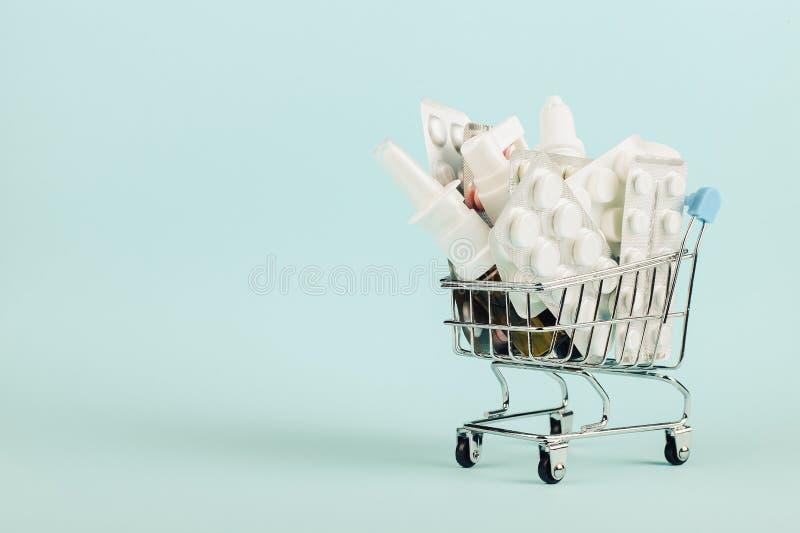 Carrinho de compras carregado com os comprimidos em um fundo azul O conceito da medicina e a venda das drogas Copie o espa?o fotos de stock