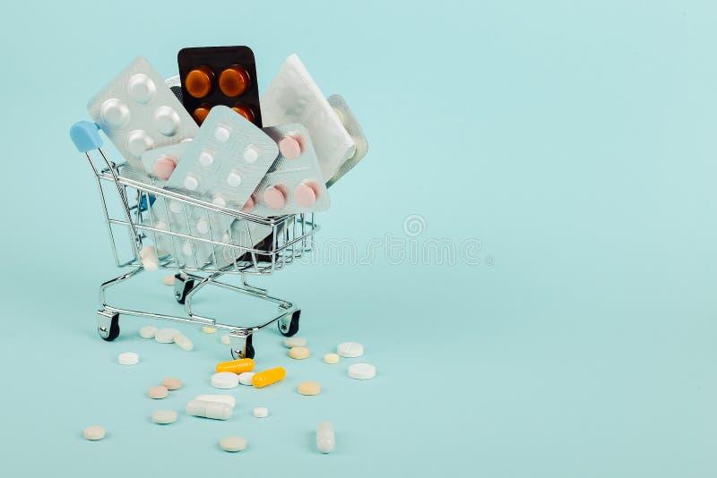 Carrinho de compras carregado com os comprimidos em um fundo azul O conceito da medicina e a venda das drogas Copie o espa?o fotografia de stock