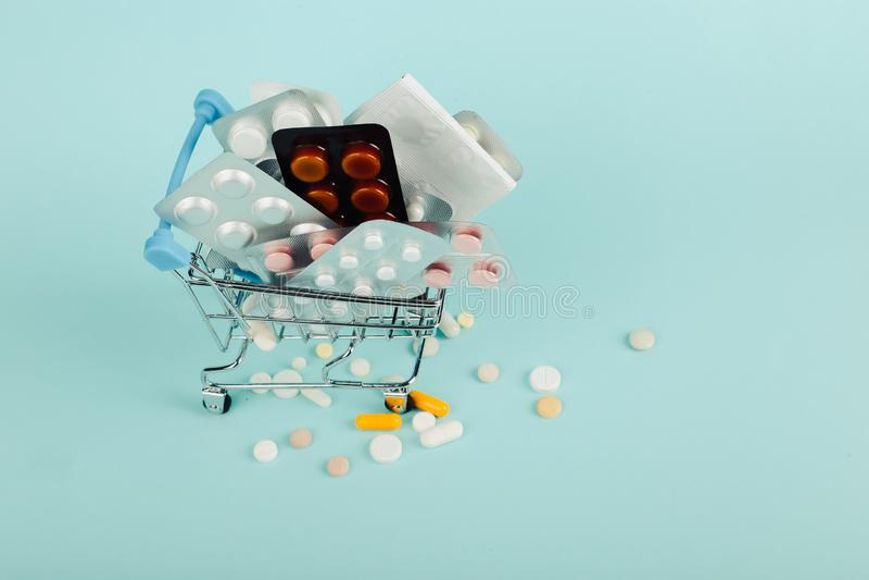 Carrinho de compras carregado com os comprimidos em um fundo azul O conceito da medicina e a venda das drogas Copie o espa?o fotos de stock royalty free