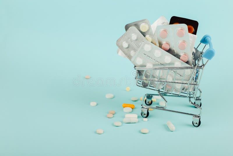 Carrinho de compras carregado com os comprimidos em um fundo azul O conceito da medicina e a venda das drogas Copie o espa?o imagem de stock royalty free