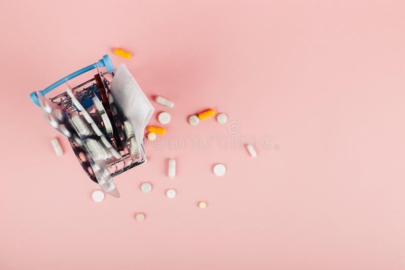 Carrinho de compras carregado com os comprimidos em um fundo cor-de-rosa O conceito da medicina e a venda das drogas Copie o espa foto de stock royalty free