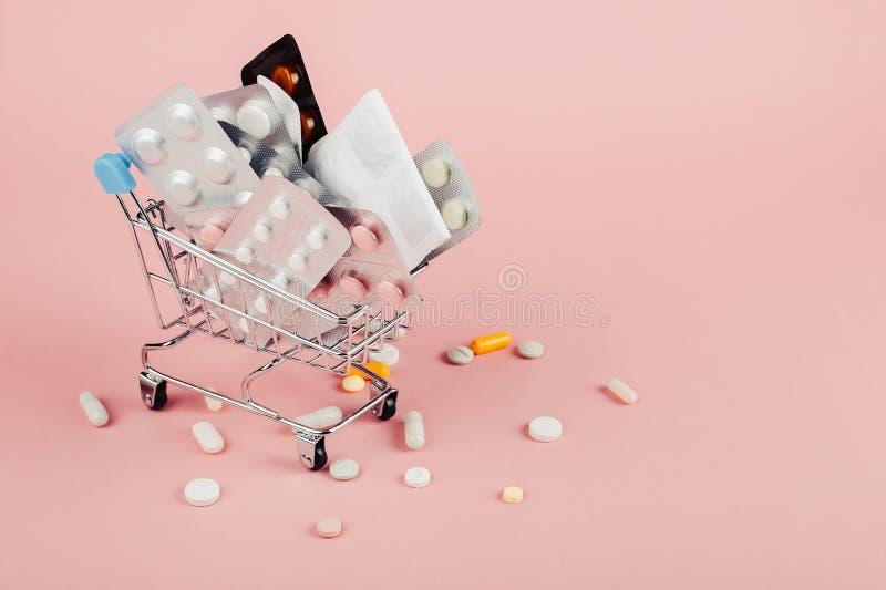 Carrinho de compras carregado com os comprimidos em um fundo cor-de-rosa O conceito da medicina e a venda das drogas Copie o espa imagens de stock