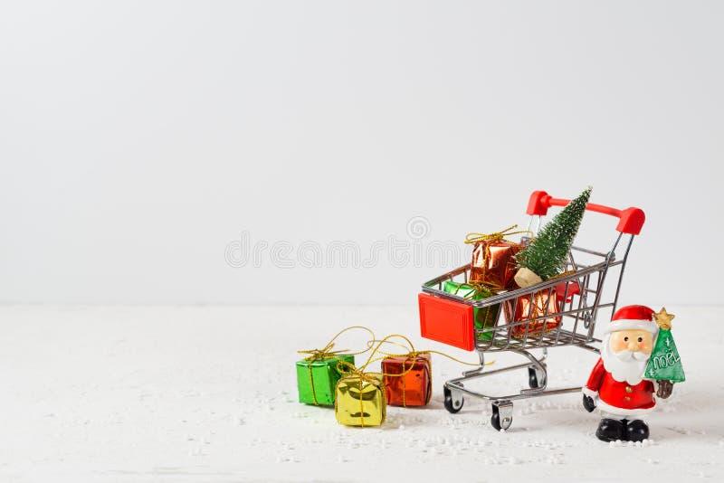 Carrinho de compras com árvore de natal e caixas de presentes em miniatura e Santa Cláusula sobre mesa de madeira Horário de comp fotos de stock
