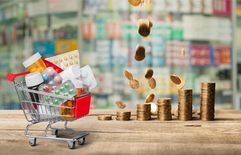 Carrinho de compras com comprimidos e as moedas empilhadas fotografia de stock royalty free