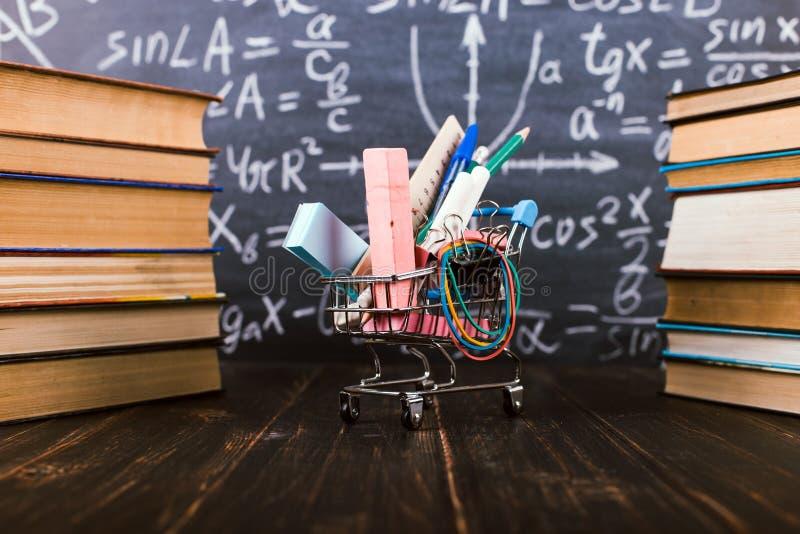 Carrinho de compras com fontes de escola, na tabela com livros na perspectiva de um quadro Conceito de volta ? escola fotografia de stock royalty free