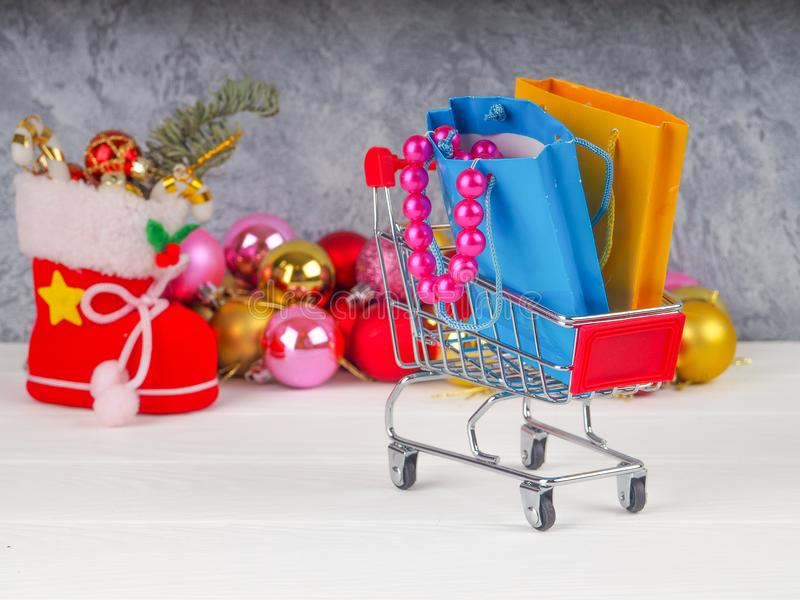 Carrinho de compras com presentes e presentes do Natal, venda do Natal e do ano novo fotografia de stock