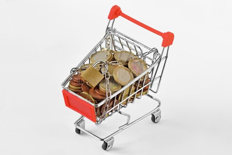 Carrinho de compras completamente do dinheiro com corrente e do cadeado no fundo branco - conceito da economia e da segurança, c imagem de stock