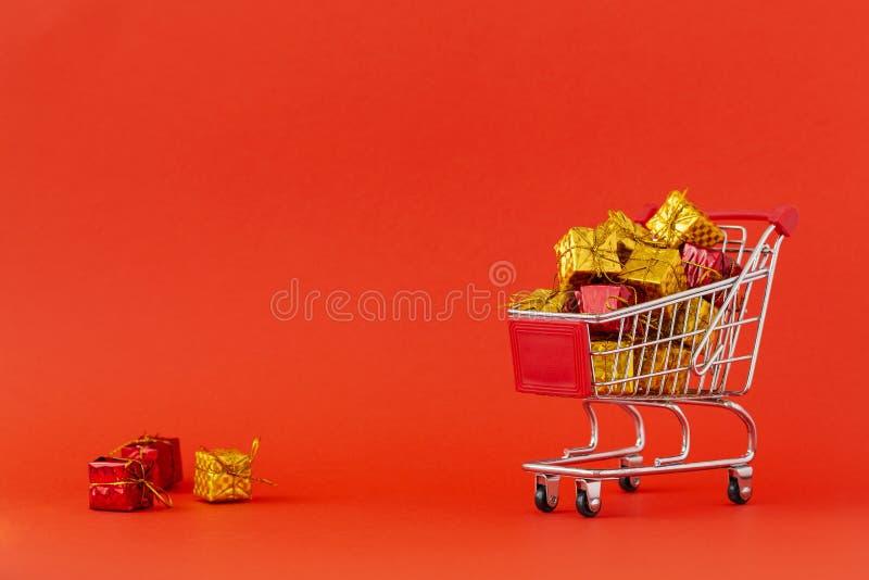 Carrinho de compras completamente dos presentes no fundo vermelho Close-up do trole de compra sobre com algum espaço da cópia Con imagens de stock
