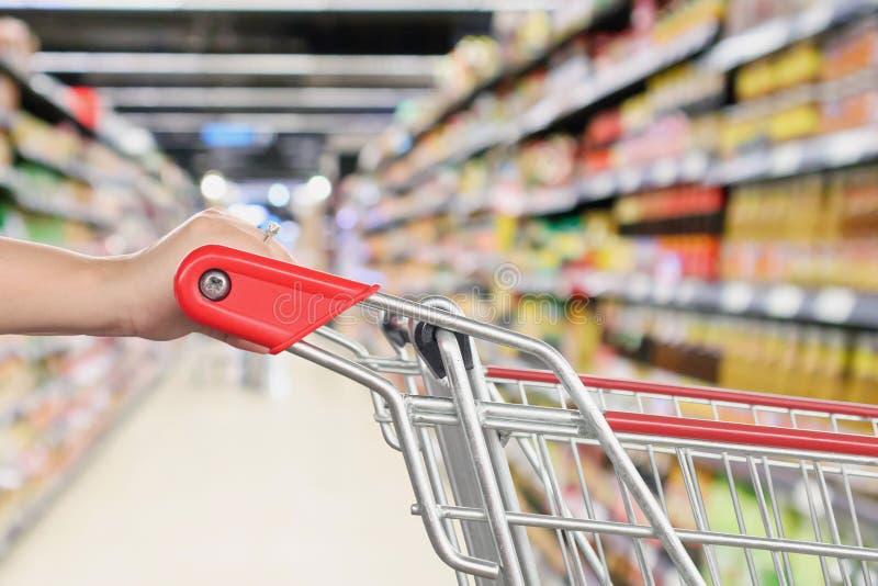 Carrinho de compras da posse da mulher com o corredor abstrato da loja de desconto do supermercado do borrão fotografia de stock