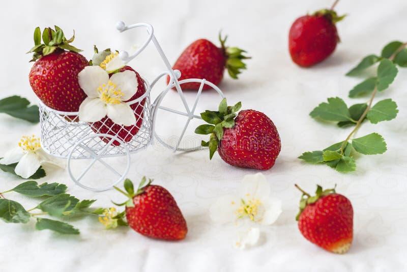 Carrinho de compras diminuto do brinquedo, trole com morangos maduras, folhas, flores no fundo claro Conceito do vegetariano fotos de stock