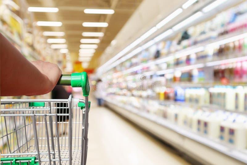 Carrinho de compras do supermercado da posse da mão da mulher com as prateleiras abstratas do refrigerador do borrão fotos de stock