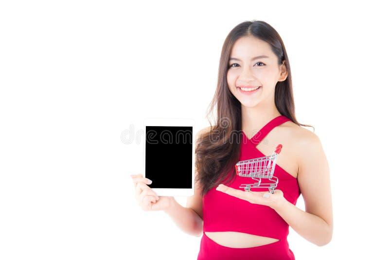 carrinho de compras e tabuleta que mantêm disponível a mulher asiática isolada imagens de stock