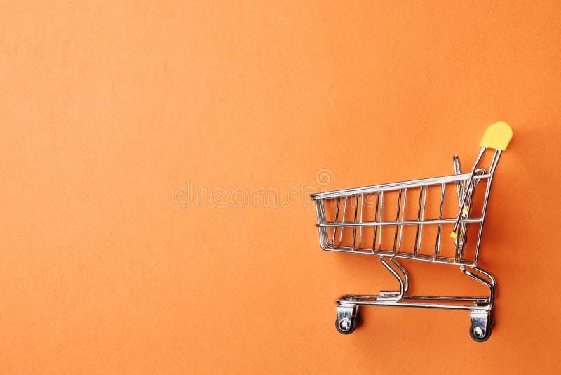 Carrinho de compras em um fundo alaranjado fotografia de stock royalty free