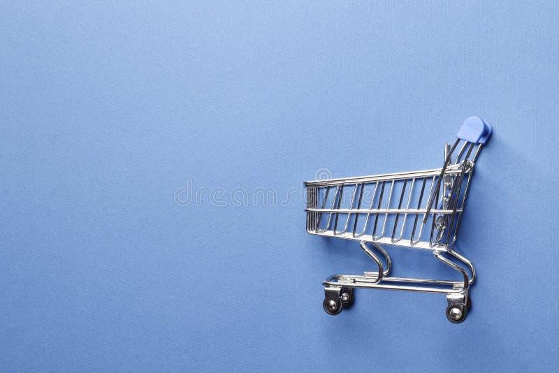 Carrinho de compras em um fundo azul fotografia de stock