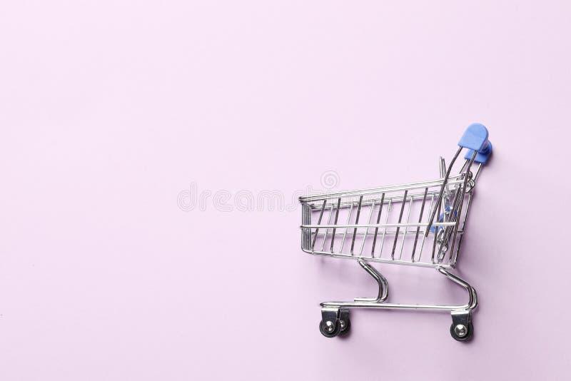 Carrinho de compras em um fundo cor-de-rosa imagem de stock