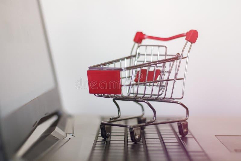 Carrinho de compras em um portátil conceito em linha da compra e do comércio eletrônico fotografia de stock