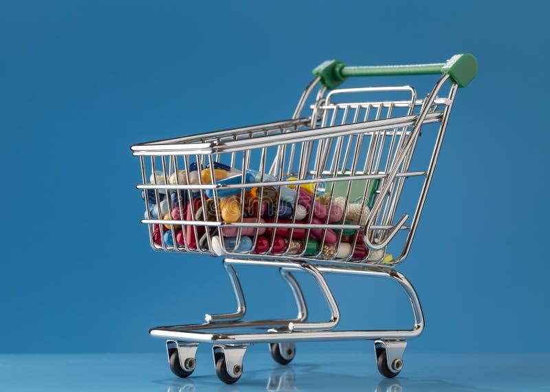 Carrinho de compras enchido com os comprimidos coloridos e as cápsulas foto de stock royalty free
