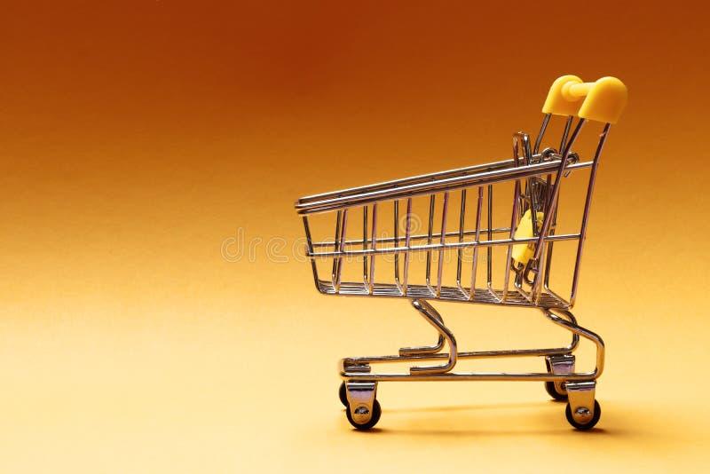 Carrinho de compras no fundo amarelo imagem de stock
