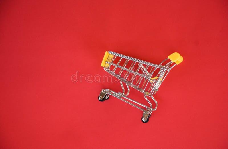 Carrinho de compras no fundo vermelho/conceito de compra em linha com o carrinho de compras amarelo na vista superior - férias da imagem de stock
