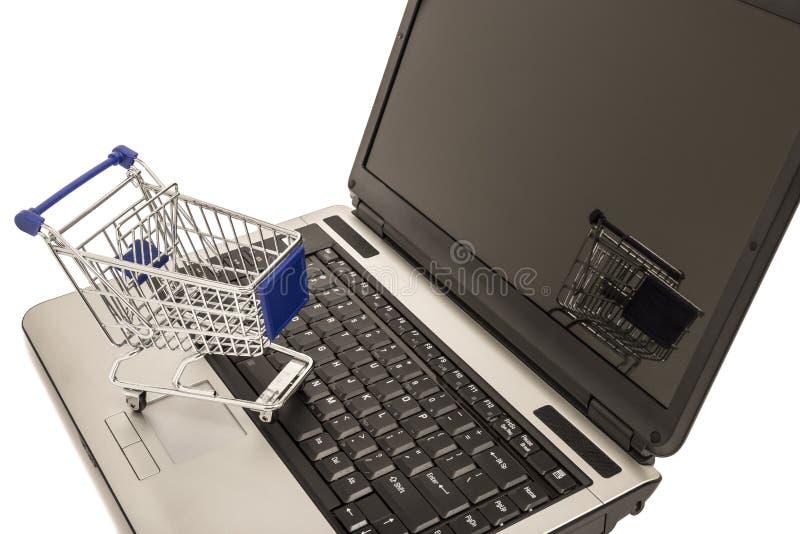 Carrinho de compras no portátil aberto com reflexão fotos de stock