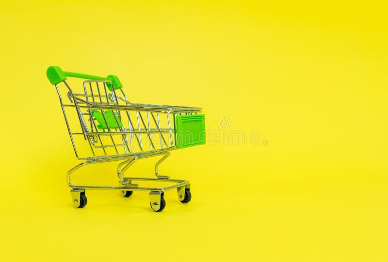 Carrinho de compras no supermercado em um amarelo fotografia de stock royalty free