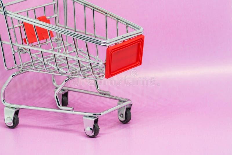 Carrinho de compras ou trole do metal do brinquedo no fundo do rosa do inclinação com espaço da cópia fotos de stock