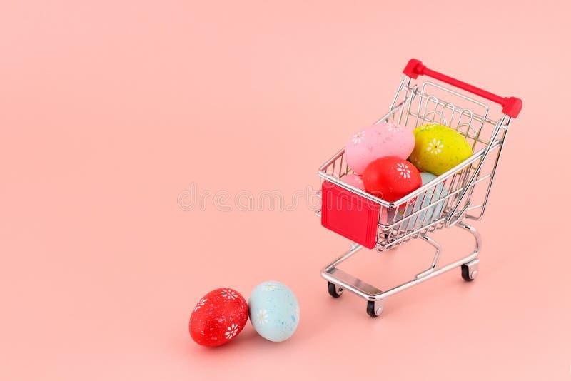 Carrinho de compras pequeno com os ovos pintados coloridos em um fundo cor-de-rosa com grande espaço da cópia para o texto Concei imagens de stock