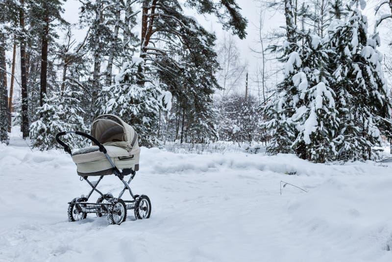 Carrinho de criança infantil do bebê na neve na floresta do inverno está frio Sono infantil do bebê dentro do pram no ar fresco fotografia de stock