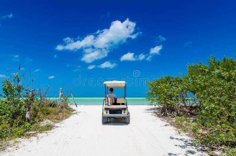 Carrinho de golfe da equitação do homem na praia branca tropical fotos de stock royalty free