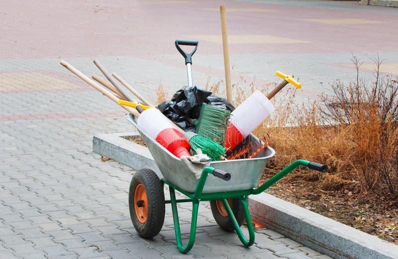 Carrinho de m?o de duas rodas com as ferramentas para a limpeza, molhar e os trabalhos do jardim no parque imagens de stock royalty free