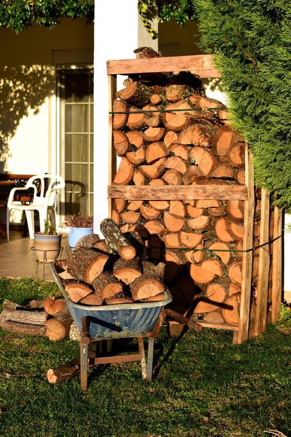 Carrinho de mão e pálete de roda completamente das madeiras para o inverno no jardim fotografia de stock