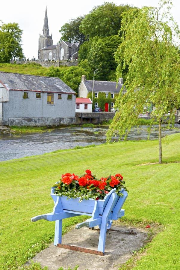 Carrinho de mão de roda no parque e na igreja do castletownroche fotos de stock royalty free