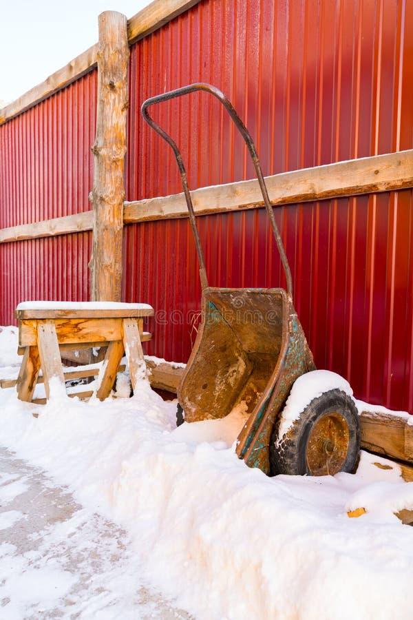 Carrinho de mão velho com neve fotografia de stock