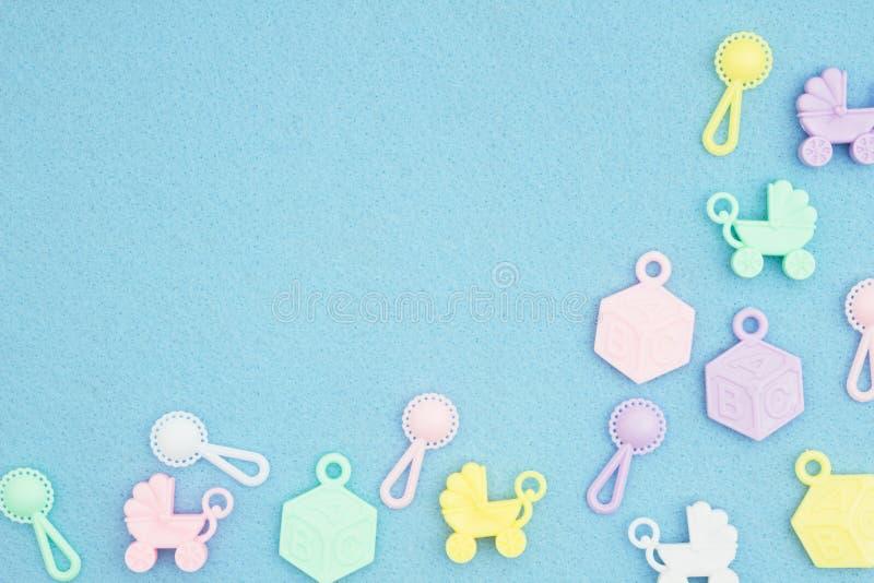 Carrinhos de crian?a de beb?, blocos do ABC e chocalhos em um fundo material textured do azul imagem de stock