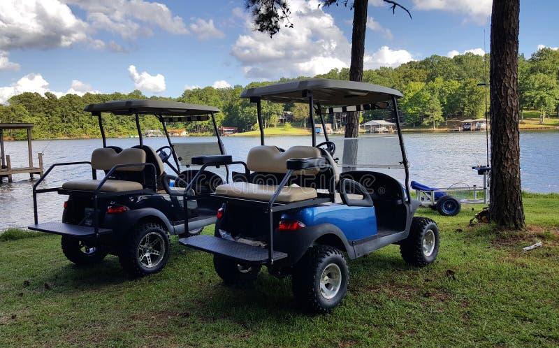 Carrinhos de golfe pelo lago imagens de stock royalty free
