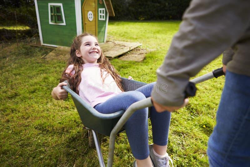 Carriola del giardino di Pushing Sister In del fratello fotografia stock libera da diritti