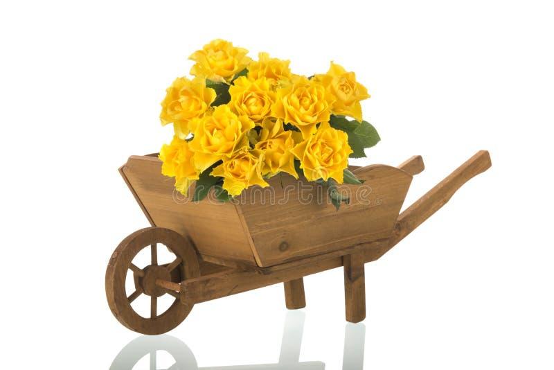 Carriola di ruota con le rose gialle immagine stock