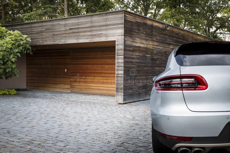 Carro agradável de SUV do esporte na frente de uma garagem imagens de stock