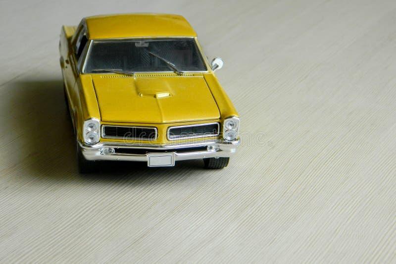 Carro amarelo do brinquedo na superfície listrada cinzenta Modelo do carro clássico do músculo com sombras e foco em parte macio  foto de stock