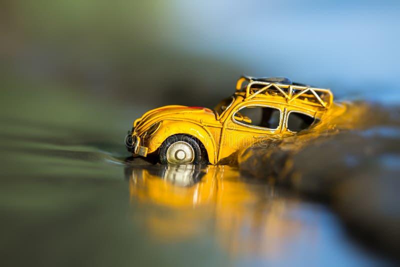 Carro amarelo pequeno do brinquedo no oceano imagens de stock