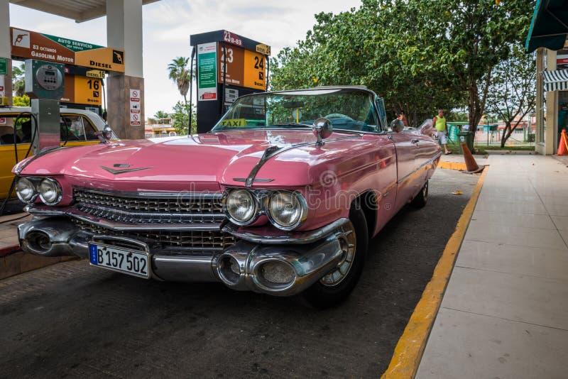 Carro americano cor-de-rosa do vintage no posto de gasolina em Havana Cuba foto de stock royalty free