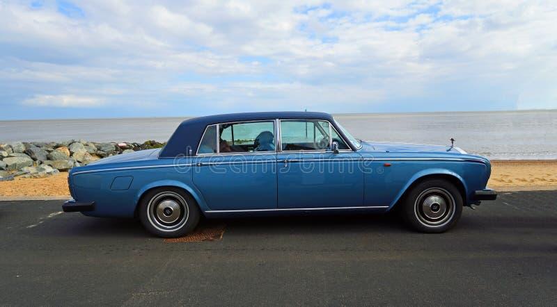 Carro azul clássico do motor de Rolls Royce estacionado no passeio da frente marítima com praia e no mar no fundo imagens de stock