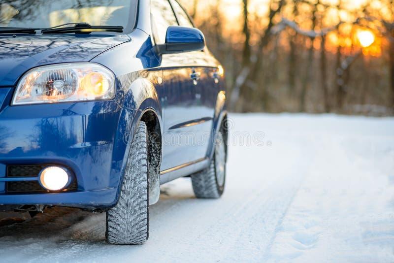 Carro azul com os pneus do inverno na estrada nevado Conduza o cofre forte fotos de stock royalty free