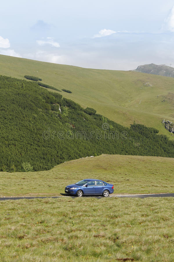 Carro azul do sedan na estrada da montanha foto de stock